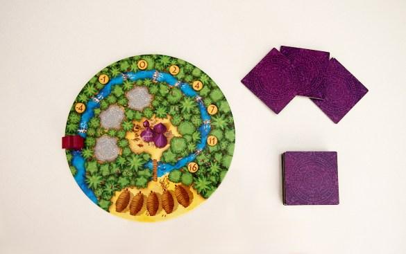 Antes de empezar, cada jugador recibe su tablero de aldea, una figura de aguador y sus losetas de recolectores (la mano estará formada por tres de ellas).