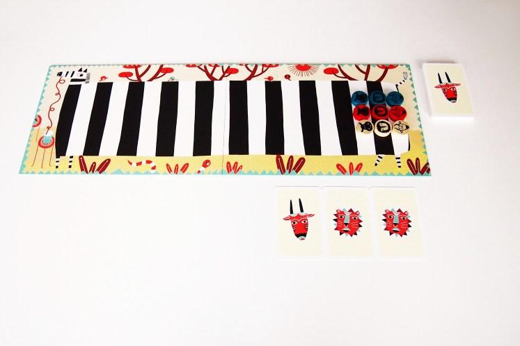 Antes de empezar, cada jugador coloca a sus tres animales en sus respectivas casillas. Se reparten, además, tres cartas.