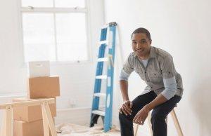 Black man sitting in room under renovation