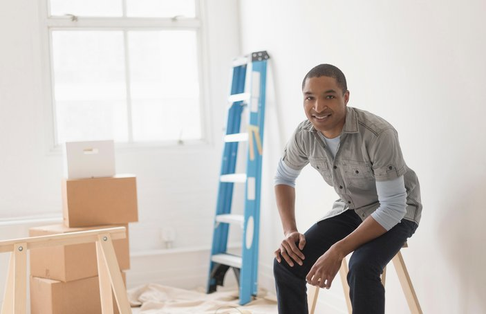 Black man sitting in room under renovation
