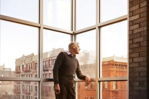 Man looking away while standing by window at home