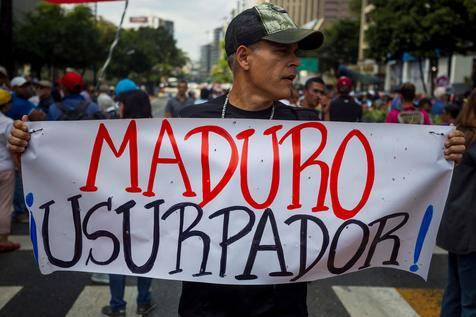 A man holds a sign that reads 'Maduro usurper' during a protest against Nicolas Maduro's Government, in Caracas, Venezuela, 11 January 2019. President of the Venezuelan National Assembly Juan Guaido demanded the support of citizens, members of the military, and the international community to take control of the Executive. EPA/MIGUEL GUTIERREZ