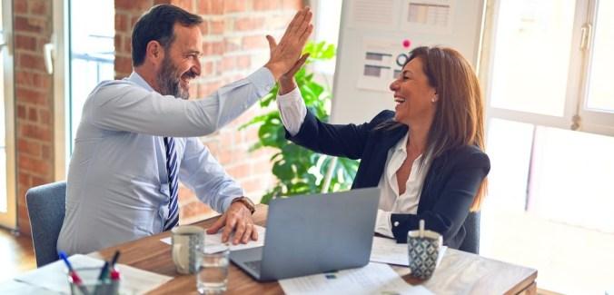 Kollegor gör high five i glädjen över att förstå bokföringslagen