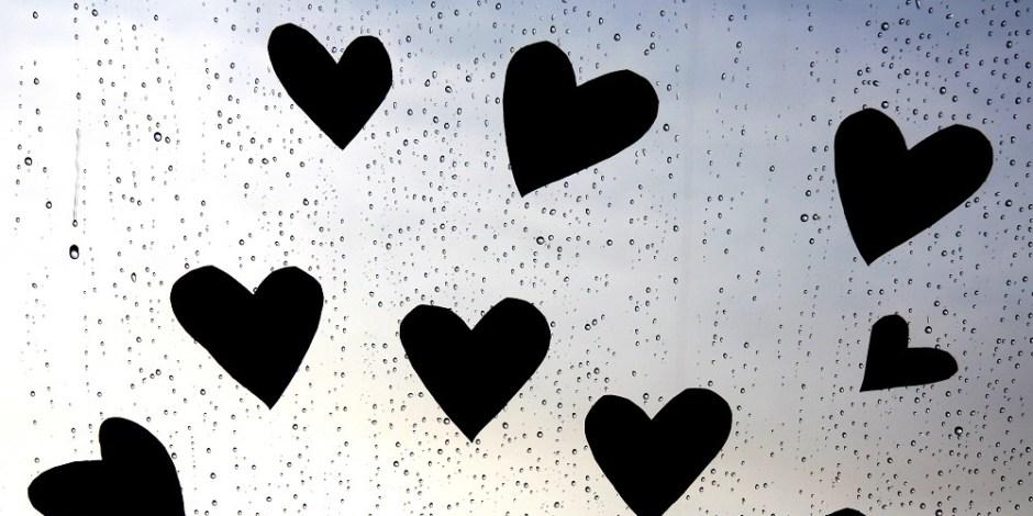 Corações cortados em papel preto estão colados ao vidro de uma janela. Chove do lado de fora.