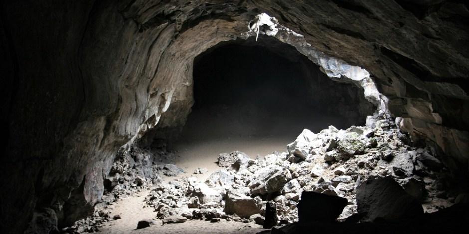 Entrada misteriosa de uma caverna. A entrada está cheia de pedras caídas onde um pouco de luz ainda pode ser refletida, mas a partir daí é tudo escuridão.