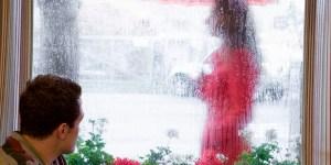 Um homem bebe café em um restaurante, olhando para fora pela janela, enquanto uma mulher vestida de vermelho passa pela calçada, na chuva, com seu guarda-chuva.