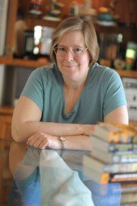 Lois McMaster Bujold em frente à uma mesa com alguns livros