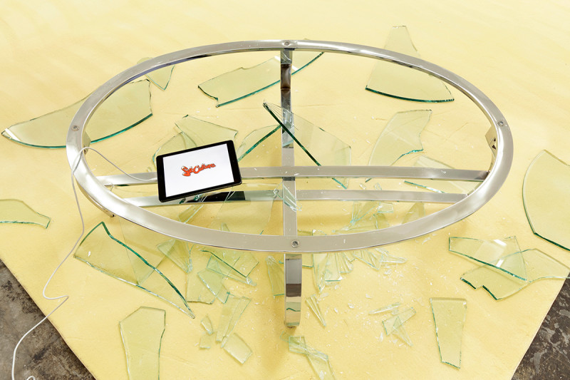 Juliana Paciulli, Let's Make a Subculture.............(2016). Looping video on iPad, broken glass, coffee table, carpet. Dimensions variable. Image courtesy of the artist and Greene Exhibitions.