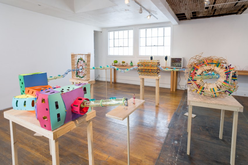 JLS (Jennifer laub Smasher) (installation view) (2015). K'NEX, Habitrail tubes, popsicle sticks, foam sheets, ceramic 3D print figurines, electrical wire, electrical tape, dental floss, hemp, duck tape, wood, inkjet prints, cardboard, construction paper, foamcore, fabric, folding table. 2 parts: Approx. 68.5 x 156 x 152 inches; 77 x 48 x 24 inches. Photo: Ruben Diaz.