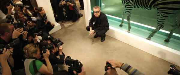 """British artist Damien Hirst poses for photographs in front of his work entitled 'The Incredible Jouney' during a photocall at Sotheby's art gallery and auction house in central London, on September 8, 2008. A unicorn, a zebra and a calf in formaldehyde are set to highlight a sale on September 15 and 16, 2008 of more than 200 works by Damien Hirst. The two-day auction, titled """"Beautiful Inside My Head Forever"""", of 223 works by the 43-year-old British modern artist, is expected to raise in excess of 65 million pounds (82.3 million euros, 129.6 million dollars), which would make it a record for any auction of works by a single artist, Sotheby's said. AFP PHOTO/Shaun Curry (Photo credit should read SHAUN CURRY/AFP/Getty Images)"""