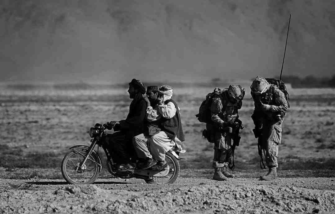 Anja Niedringhaus, Afghan men on a motorcycle overtake Canadian soldiers with the Royal Canadian Regiment during a patrol in the Panjwaii district, southwest of Kandahar, Salavat, Afghanistan, September 2010. © picture alliance / AP Images