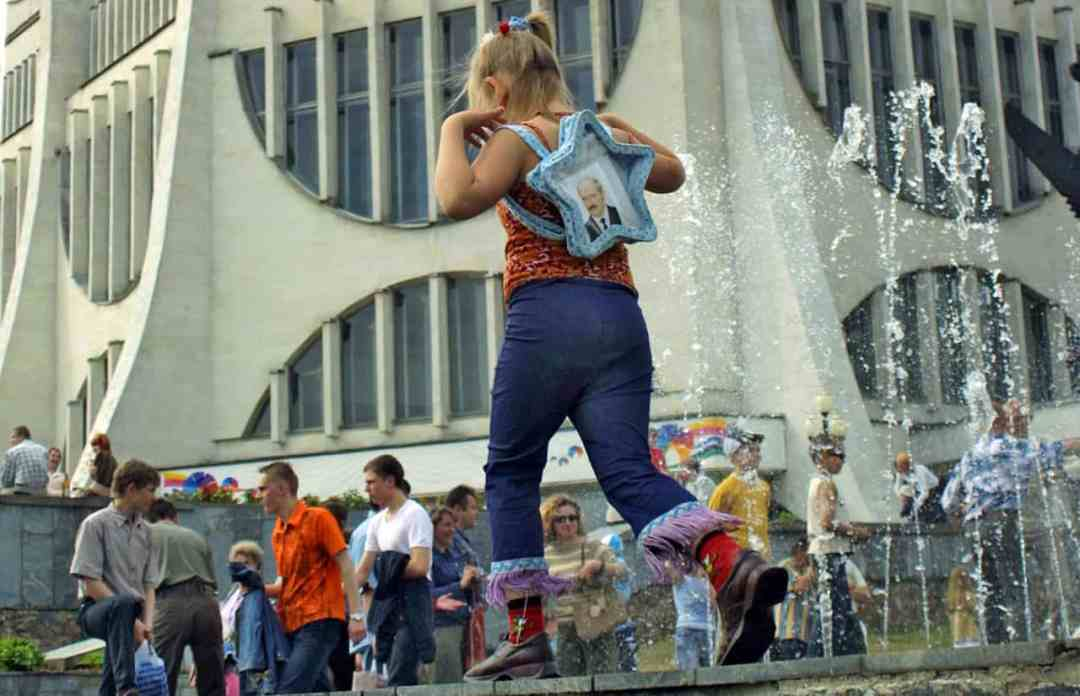 BELARUS / Grodno / June 6, 2004 / Small girl with Aleksand LukashenkoÊportrait in the bag pass away theÊfountainÊnext to the local Drama Theater. © Andrei Liankevich / Anzenberger