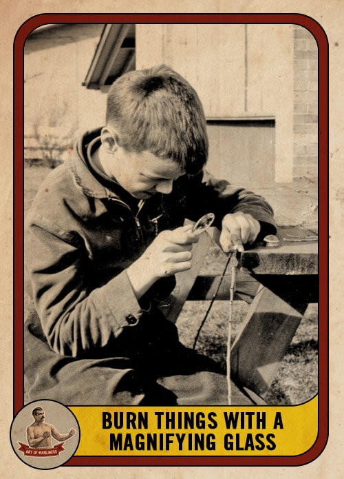 vintage boy burning a stick with a magnifying glass