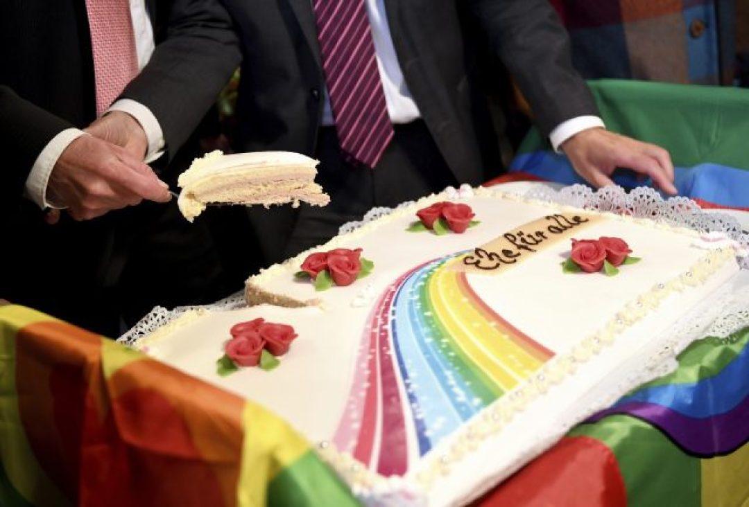 Karl Kreile, left, and Bodo Mende cut the wedding cake, in Berlin