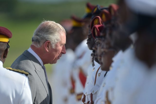 The Prince of Wales speaks to a member of the Antigua and Barbuda Defence Force and Royal Police as he arrives at VC Bird International Airport in Antigua