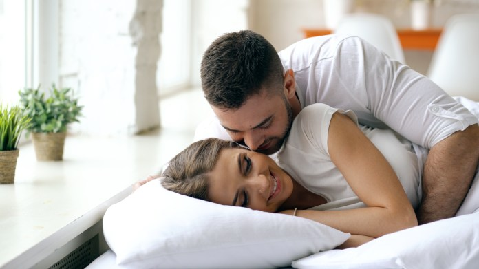 Young beautiful and loving couple wake up in the morning. Attractive man kiss and hug his wife in bed