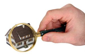 a person holding a magnifying glass over a house