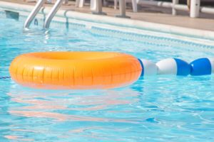 A community pool with orange inflatable innertube floating on top.