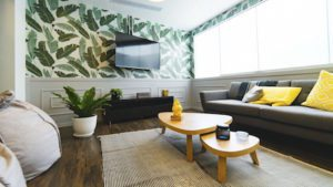 A well lit living room with a flat screen TV on the wall, a beige couch under a window, and a wooden table in the center.