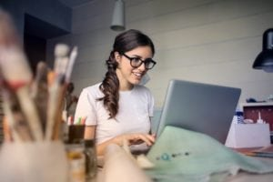 Woman smiling at a laptop as she researches the real estate market.