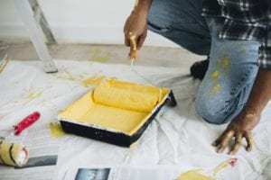 A man rolling a paint roller in a tray of yellow paint