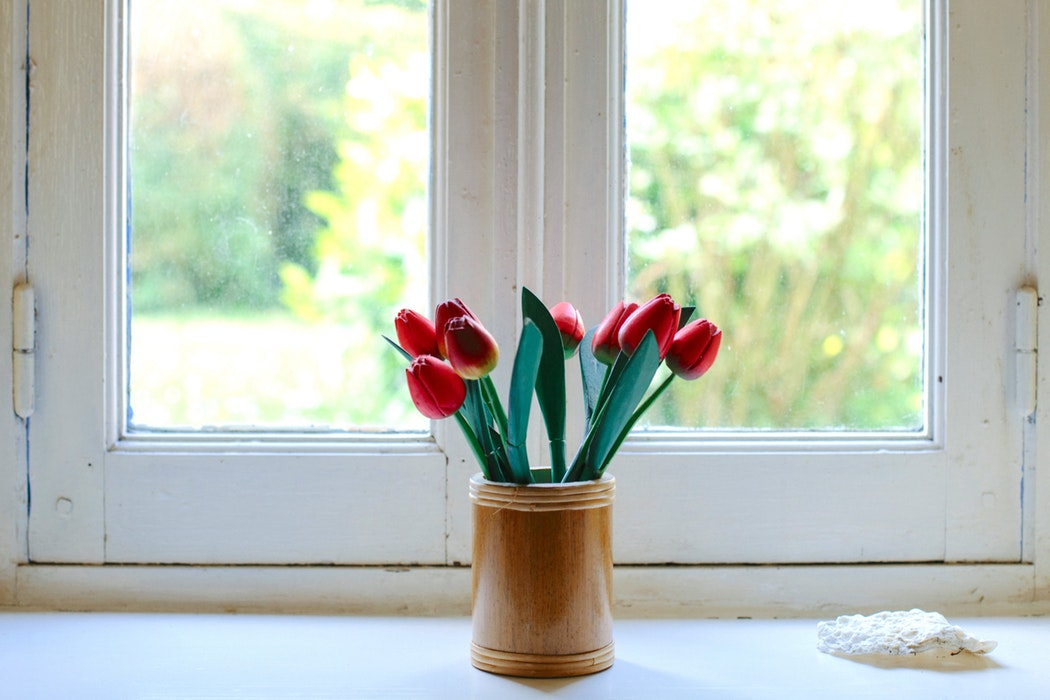 A vase of flowers in front of a cracked window.