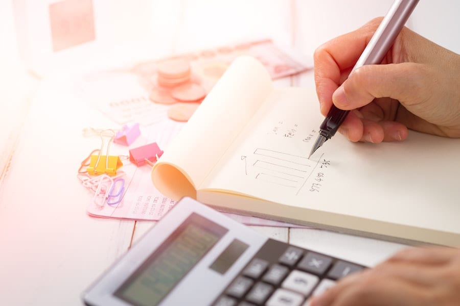 Person calculating expenses and creating a graph.