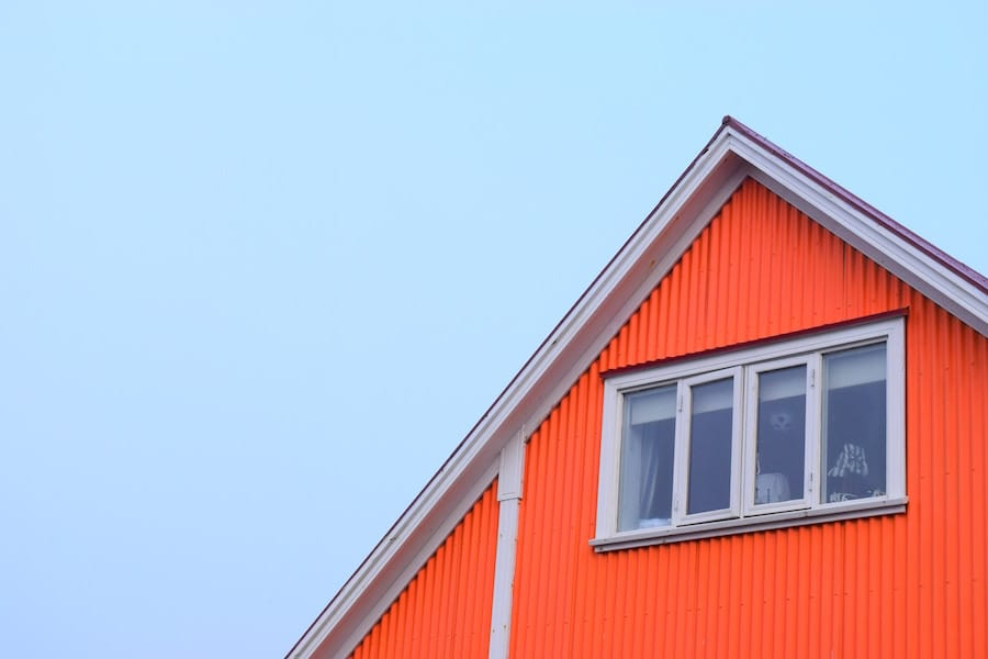 Roof of red house with window.