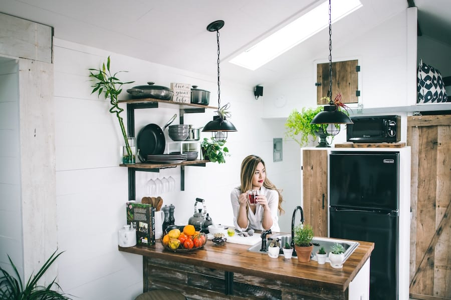 Tiny houses kitchen with woman drinking beverage