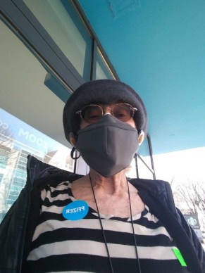 Woman in black and white shirt wearing mask.