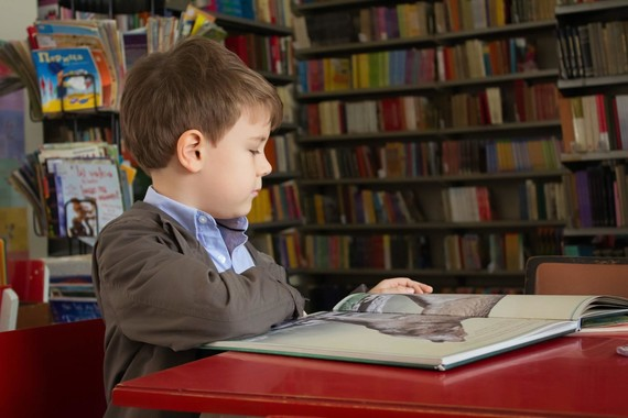 child sat reading in library