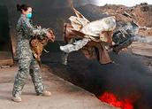 Female Service member discarding materials in a burn pit