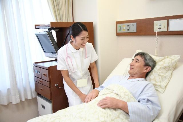 ベッドに寝ている患者と看護師