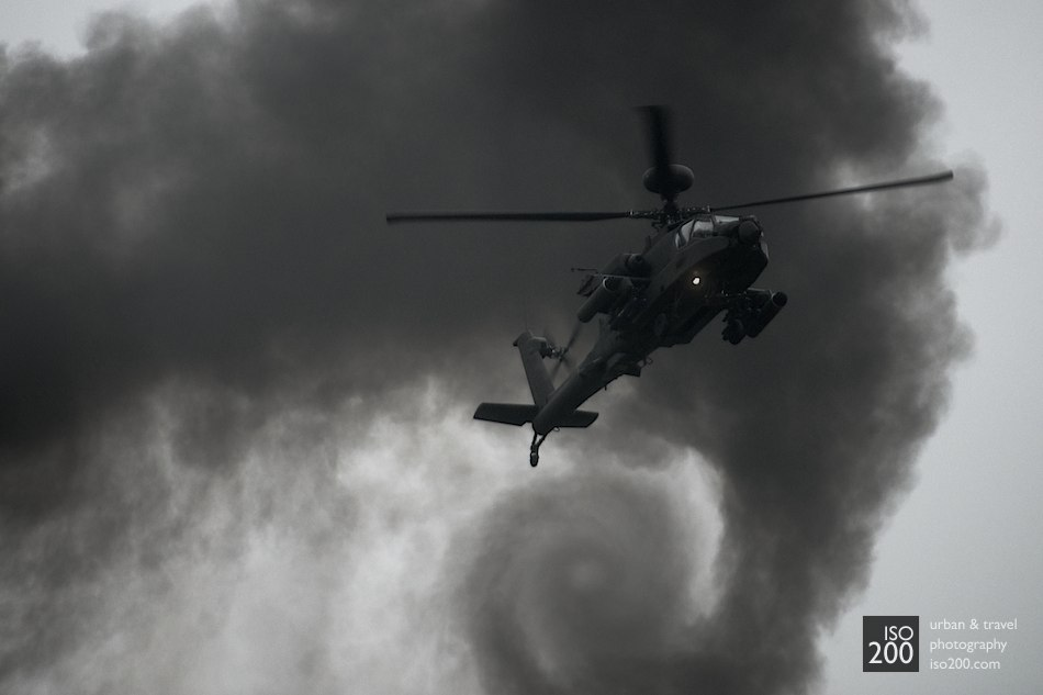 A British Army Air Corps Apache AH Mk 1attack helicopter hovers in front of swirling black clouds of smoke.
