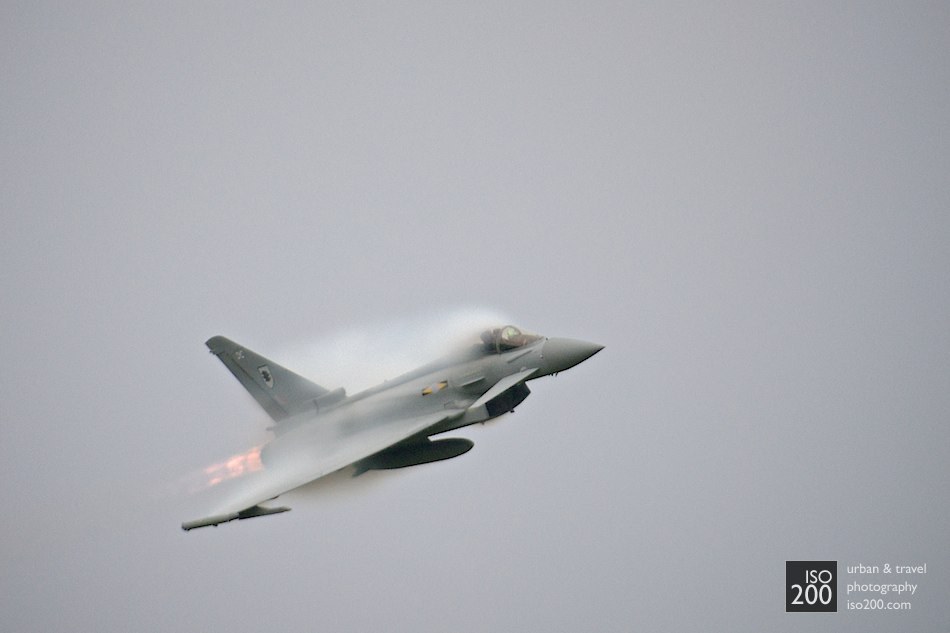 Condensation forms around the wings and cockpit of a RAF Typhoon as it pops out of a grey and dark sky. Differences in pressure above the aeroplane at high-Gs causes a temperature drop, which causes condensation.  I hope you like aeroplanes: you might be seeing a few.