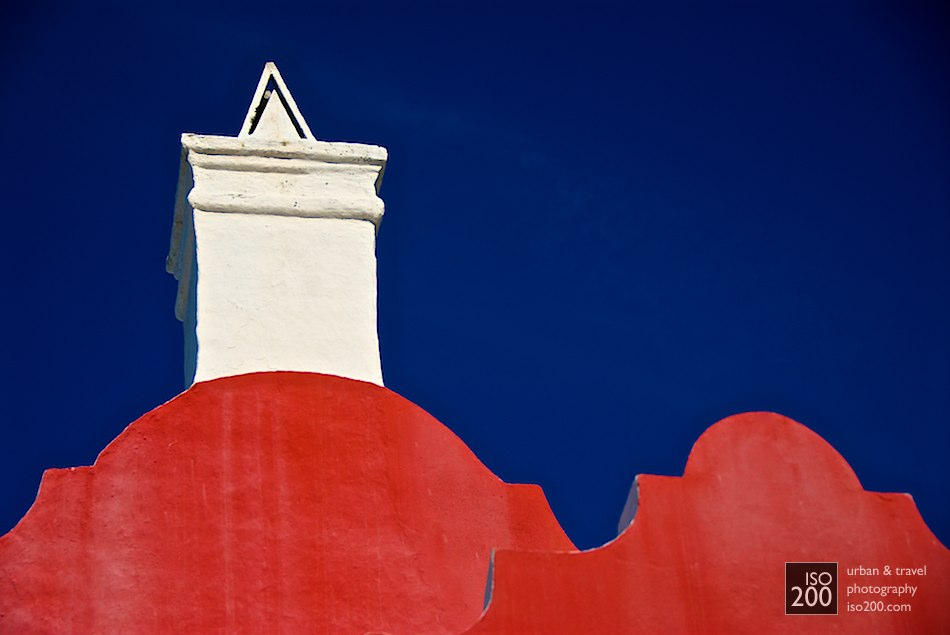 Big gable, little gable - a white chimney and coloured rounded gables on a building in Flatt's Village, Bermuda