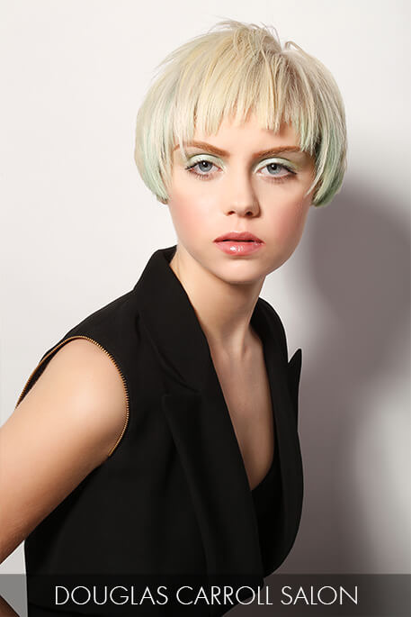 cropped cut that highlights jagged bangs and a pale green hue on platinum strands.