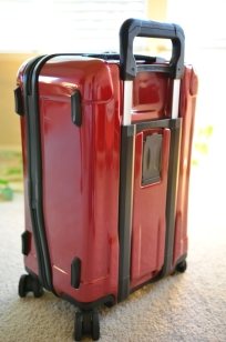 Red Briggs & Riley Torq Carry-on back corner view showing zipper curve