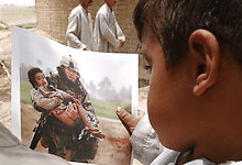 4-year-old Ali Sattar looks at a photograph that was taken of him on March 25, 2003 during the U.S. invasion of Iraq. This photo was taken July 5, 2003. (Warren Zinn -- Army Times)
