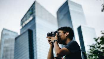 Asian guy photographing like a professional in the city