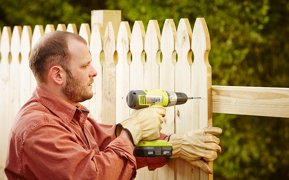 Man attaching pickets to fence post rails with a drill.
