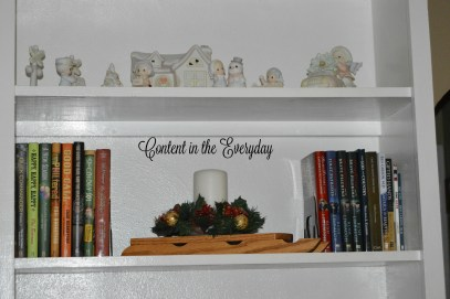 Shelf with figurines, books and candle on sled
