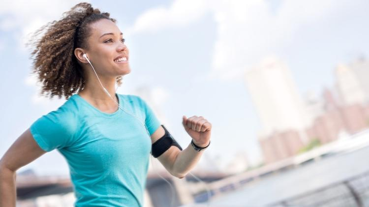 Young woman smiling and running - iStock - iStock