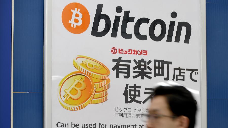homem passa por cartaz anunciando que bitcoin e aceita como forma de pagamento em loja de toquio japao 1511985320028 v2 900x506 - Bitcoin, 10 anos: Como será o futuro? Vamos pagar pizza com moeda virtual?