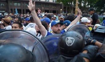 Polícia tenta conter multidão de fãs que esperam para rpestar última homenagem ao craque argentino [Foto: Ivan Pisarenko/AFP]
