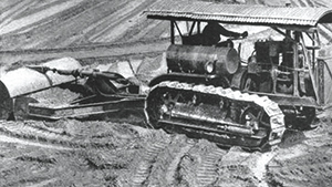 "Pre-diesel Caterpillar 60 at work on a building site towing a Killefer ""tumble bug"" scraper. Note that the elaborate canopy was a standard Caterpillar factory offering. Sixty's, both gasoline and diesel powered can be seen with the fuel tank on either side of the fender. As a general rule, fuel tank on the right is agricultural and tank on the left earthmoving but as you can see, rules were made to be broken!"