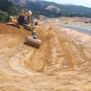 A Cat 320D excavator equipped with GPS trimming roadway batters at the Kenepuru subdivision.