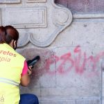 Una trabajadora del área de intendencia del Palacio de Gobierno de Morelos limpia con thinner pintas en la pared