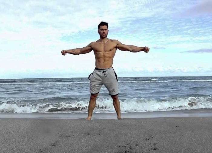 man arms spread at beach