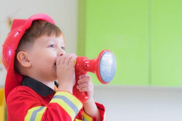 Niño vestido de bombero simulando una urgencia